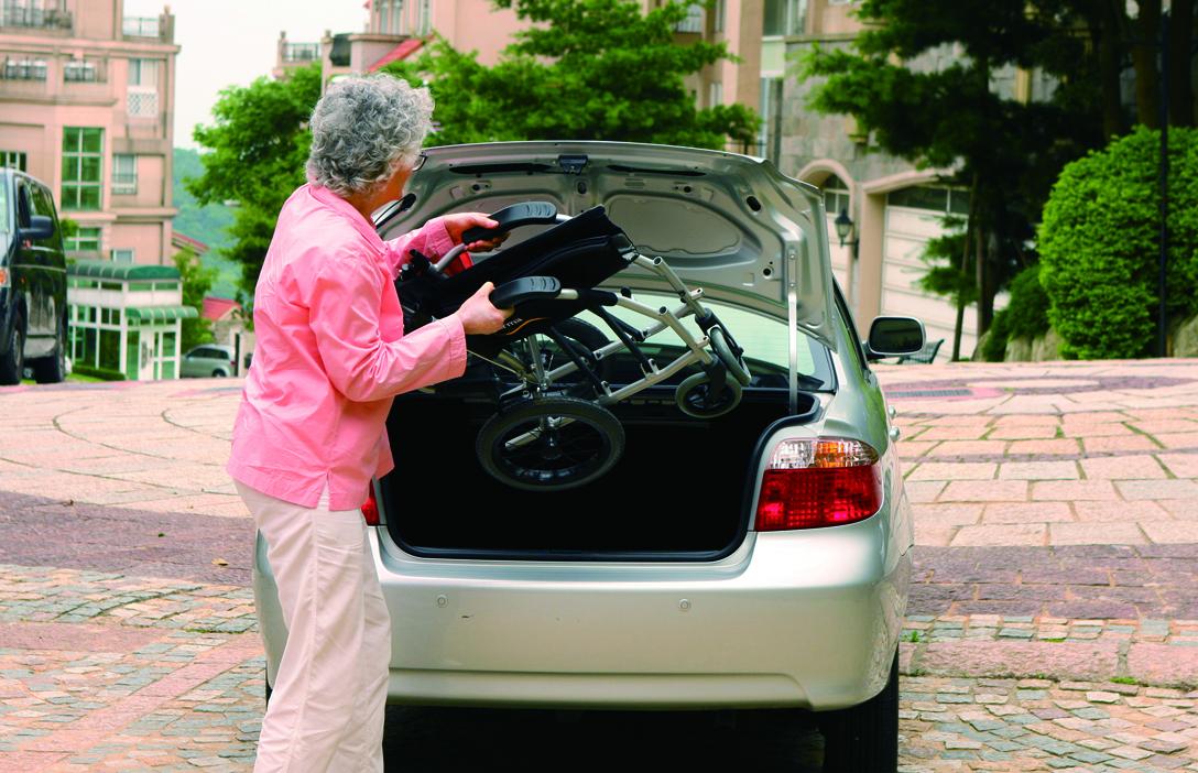Senhora a colocar cadeira de rodas manual encartada, na mala de um carro