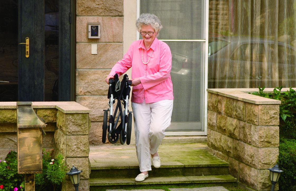Senhora a carregar cadeira de rodas manual encartada