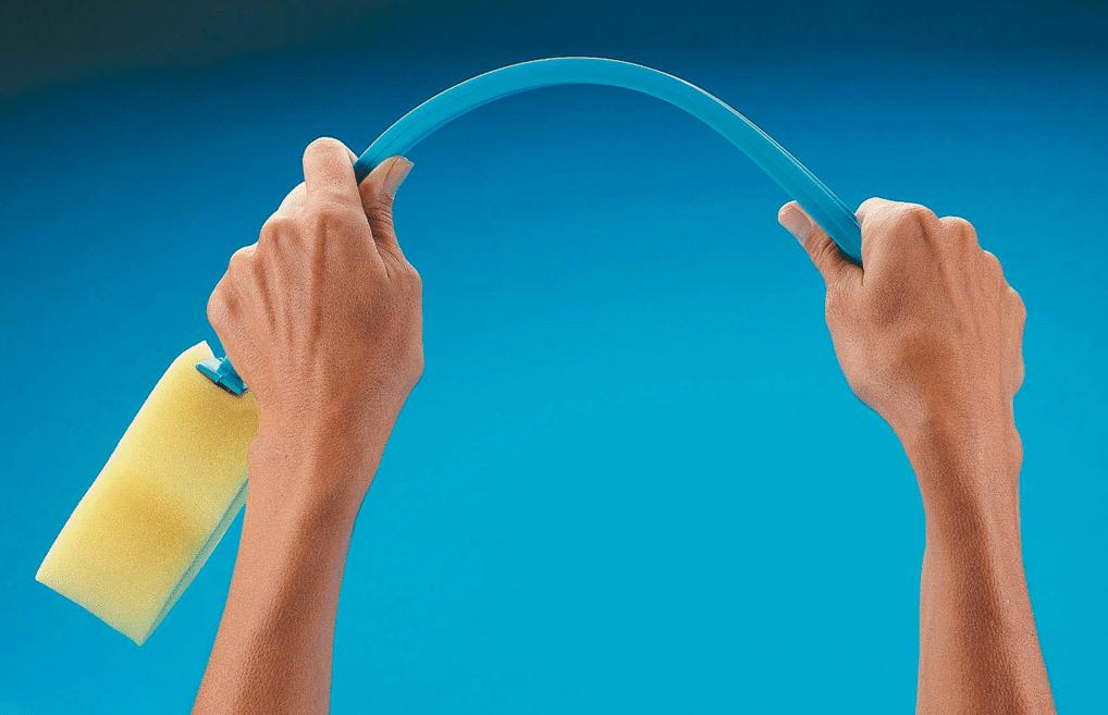 Esponja com cabo azul, dobrável para facilitar a lavagem.