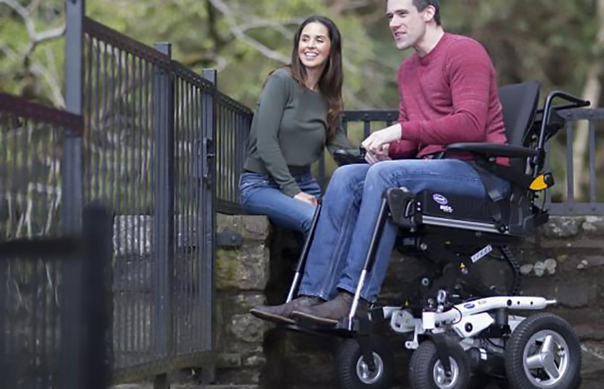 Utilizador de cadeira de rodas elétrica com acompanhante