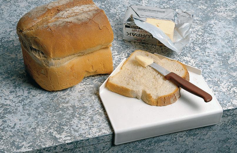 Pão em cima de tábua para facilitar a untar manteiga