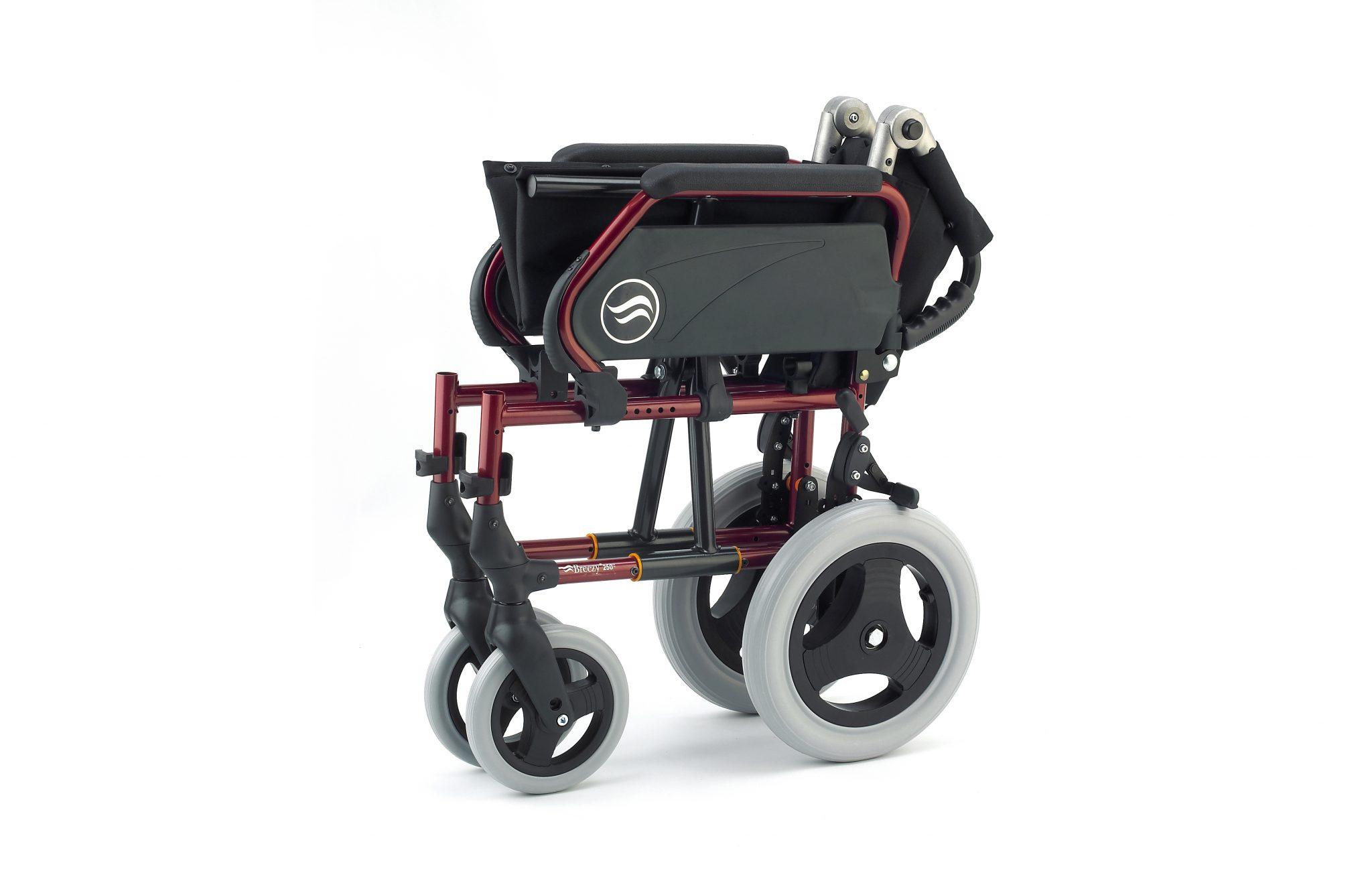 Cadeira de rodas manual, preta com estrutura vermelha, com roda pequena, encartada, com vista lateral.