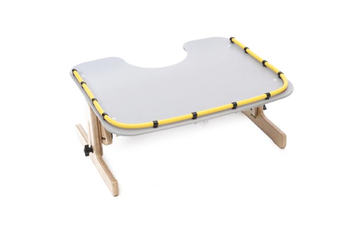 Therapy Tray da Jenx, em dois tamanhos. Uma mesa de atividades ajustável em ângulo e em altura, com recorte no centro para um melhor alcance da criança à mesa.